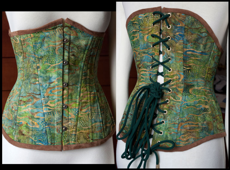 A high back underbust corset in green and blue batik cotton. It is lined with gold cotton batik and trimmed with polyester microsuede. It has a steel busk in front, and grommets and handmade silk lacing in the back. There are two layers of cotton coutil and 20 steel bones for support.
