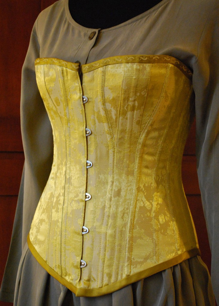 The outer fabric of this overbust corset is vintage cotton/rayon brocade. It is trimmed with embroidered antique gold silk duchesse, and lined with cotton batik. It has a steel busk in front, spiral steel bones for support, and two inner layers of cotton coutil.