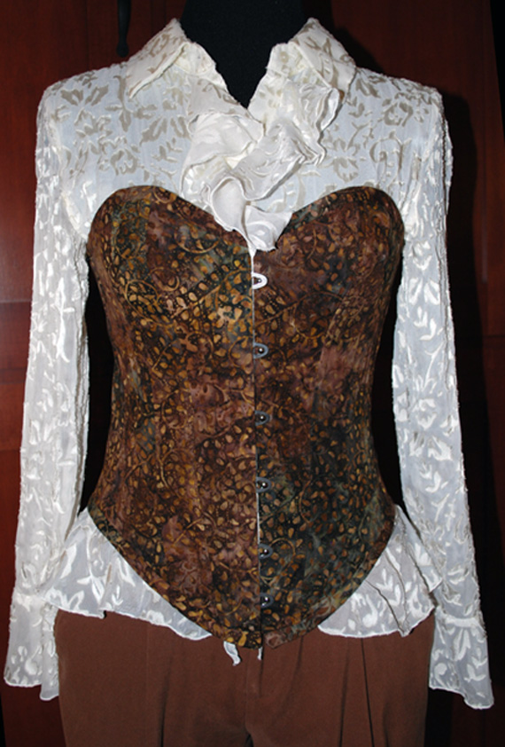 The body of this corset is made of cotton batik on the outside and two layers of black cotton coutil on the inside. It is trimmed with the same batik fabric. It is supported by a steel busk in front and 21 spiral steel bones.