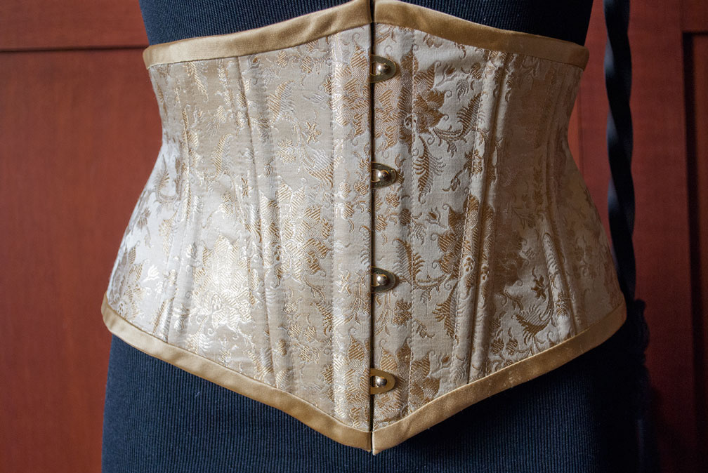 Gold metallic silk brocade waist cincher. It uses spiral and flat steel bones for stability and shaping.
